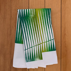 A hand block printed white flour sack towel with an opmbre of greens and yellows in a line design pattern.  Shown folded.