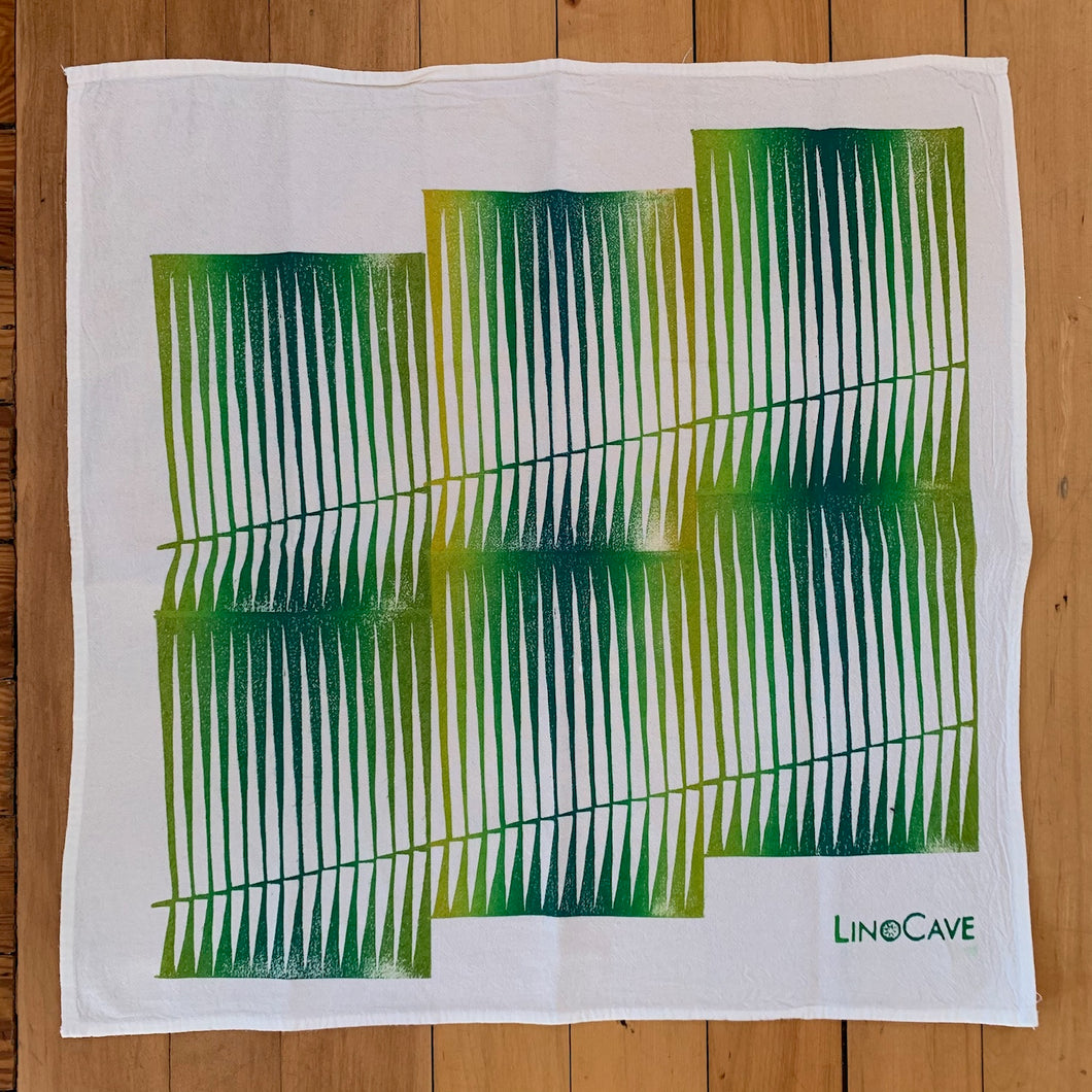 A hand block printed white flour sack towel with an opmbre of greens and yellows in a line design pattern.