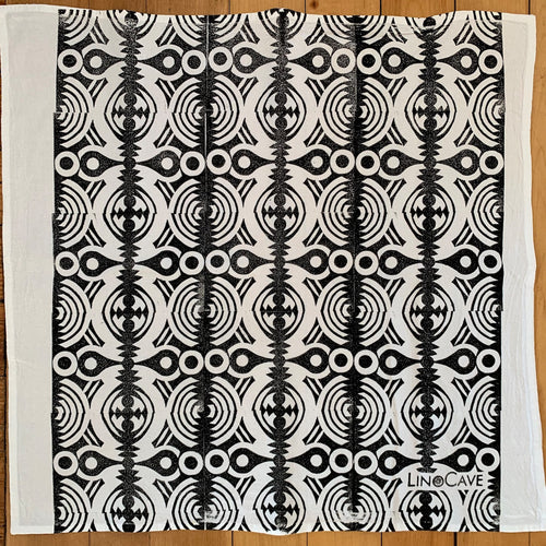 A hand block printed white flour sack towel in a black geometric pattern.