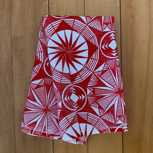 A hand block printed white flour sack towel with red in a geometric pattern.  Shown folded.