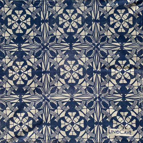 A hand block printed white flour sack towel in blue in a geometric pattern.