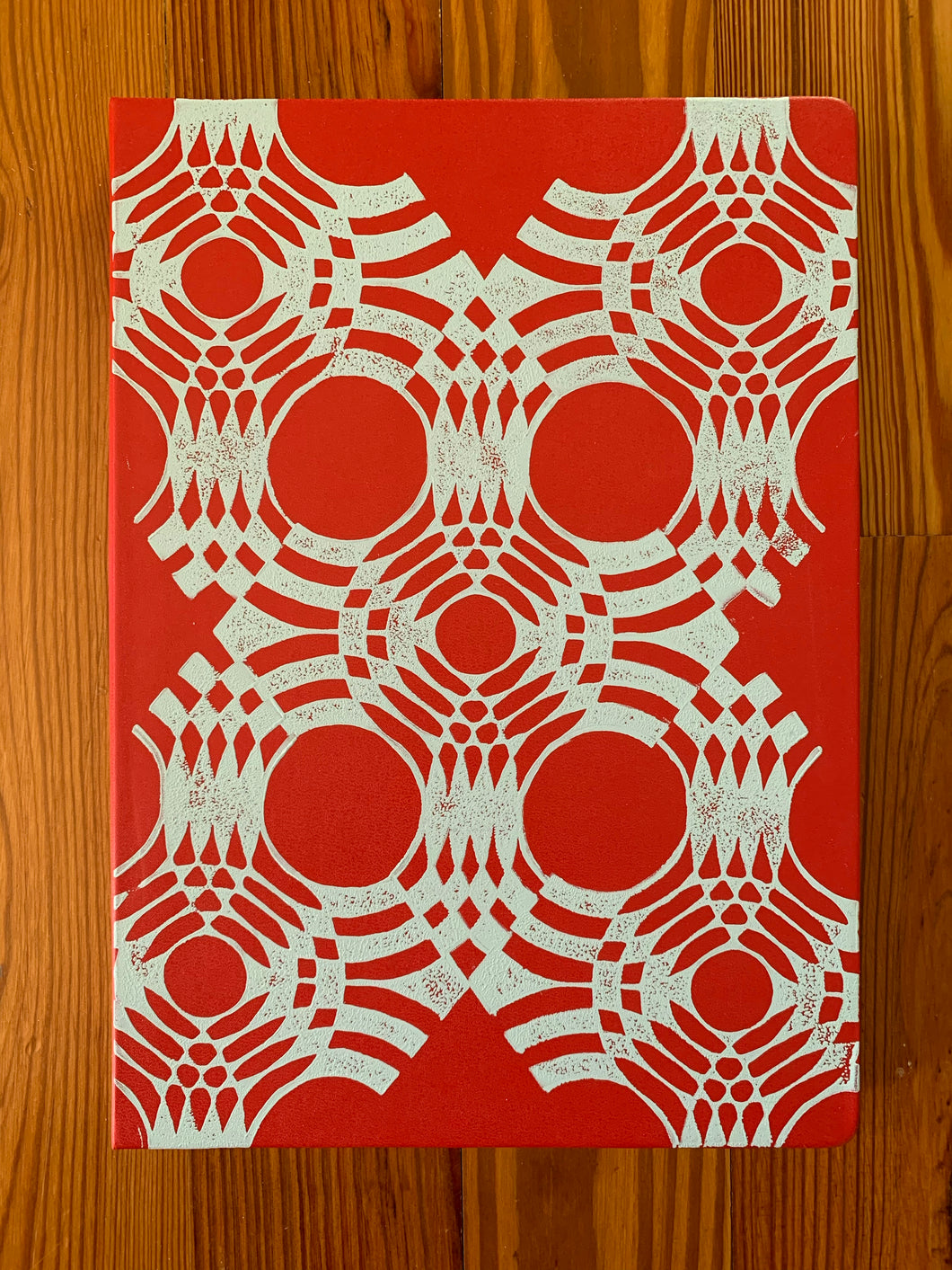 A red Moleskine sketchbook hand block printed in a white geometric pattern.