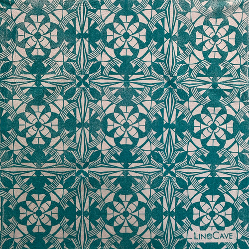 A hand block printed white flour sack towel in turquoise in a geometric pattern.