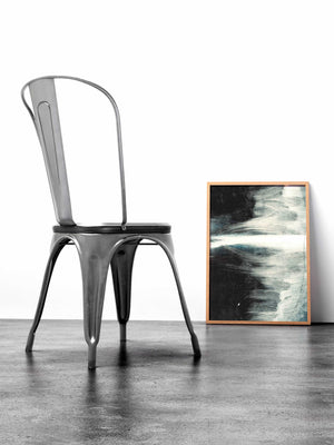 A framed abstract print  leaning against the wall next to a gray metal chair.