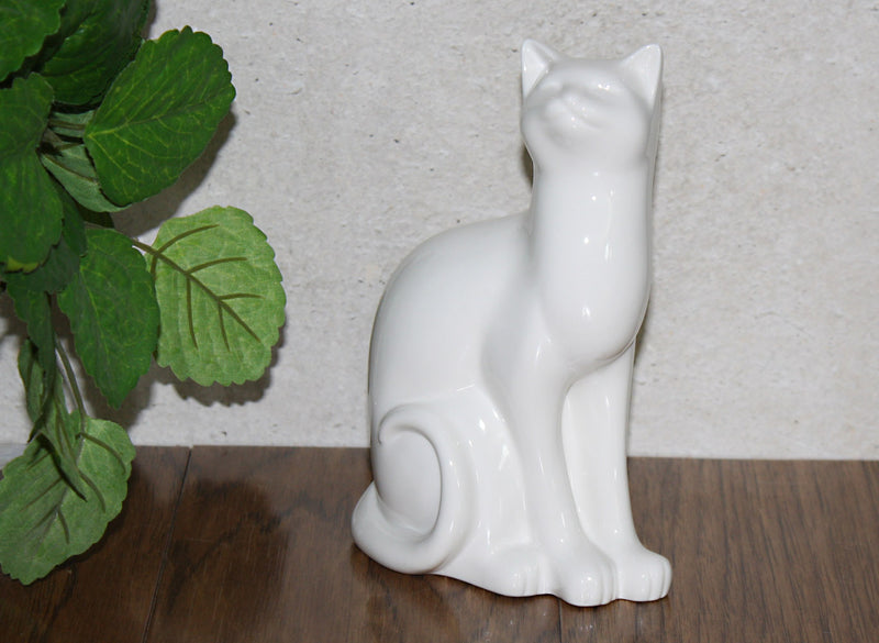 white porcelain cat sitting figurine on shelf with plant