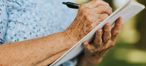 Elderly women writing on notepad.