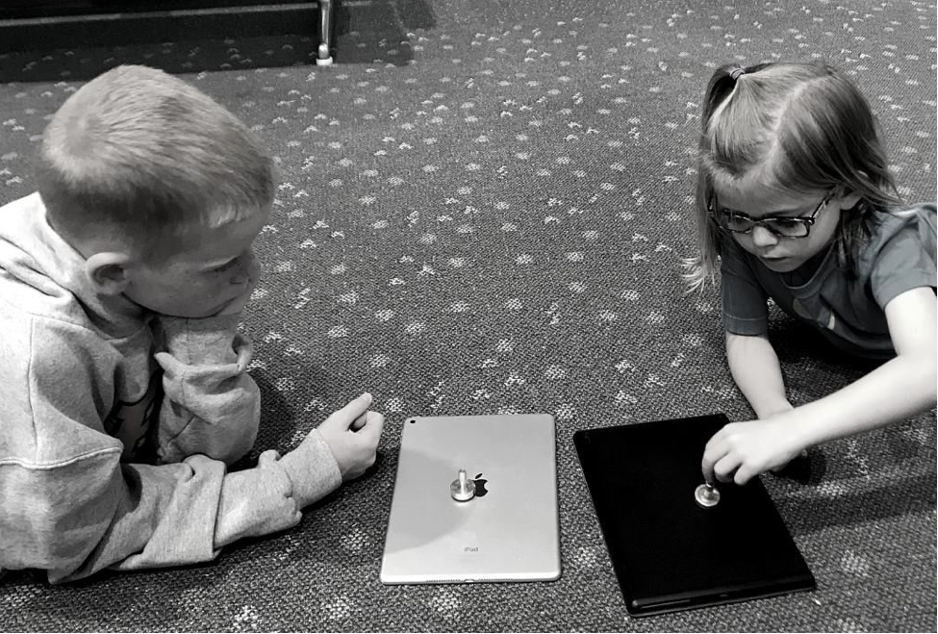 Small children play with spinning tops on the floor at an airport
