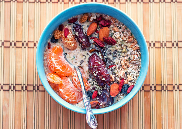 oats with fresh oranges dates almonds in blue bowl