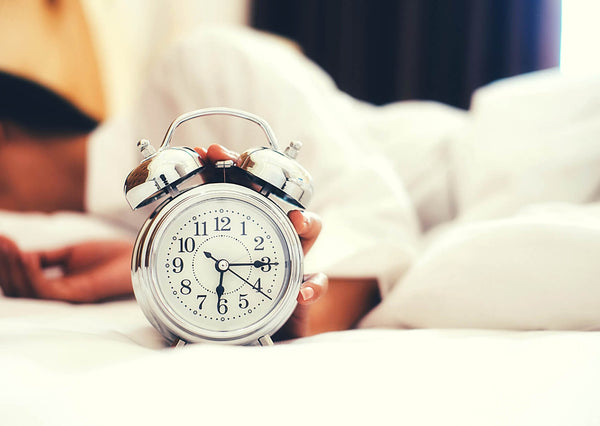 woman white shirt in bed alarm clock