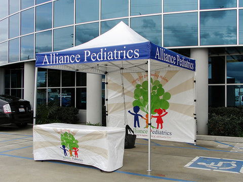 Custom 10x10 pop up tent with a printed back wall and table cover