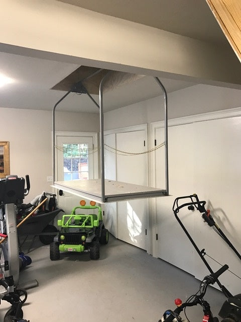 attic lift next to lawn mower