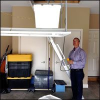 man standing next to attic lift