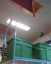 attic storage lift with two green storage tubs