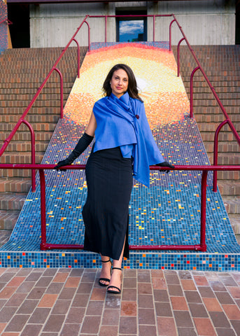 Model wearing UV sun protection sol Escape in royal blue, as a wrap, leaning back against railing.