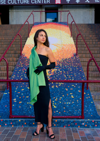 Model wearing UV sun protection sol Escape in apple green, as a sash, leaning back against railing.