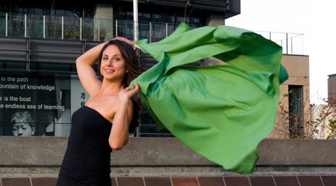 Model holding UV sun protection sol Escape in apple green with wind unfurling the cape behind her.