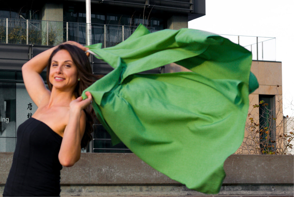 Model holding UV sun protection sol Escape in apple green with two hands, cascading in wind behind her shoulders