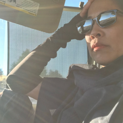 Woman in the car wearing sun glasses, sun protective arm sleeves and sol Escape UV sun protection cape.