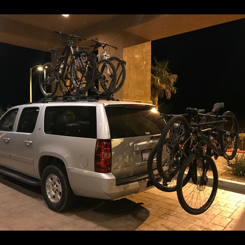 Suburban packed with three bikes on roof rack and three bikes on rear bike rack.