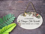"A Teacher Changes The World One Child At A Time | Oval Ceramic Wall Sign | 8 3/4"" x 6"" x 5/16"""