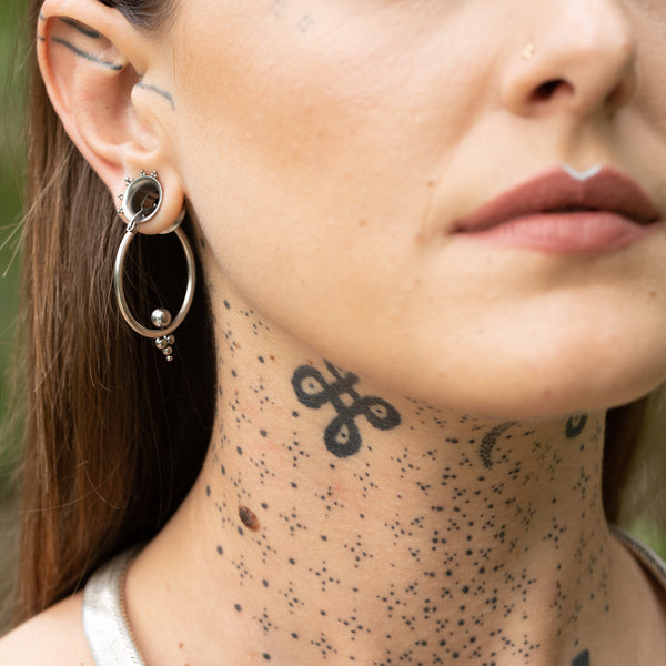Woman wearing Tribalik Ear Tunnel Jewellery & septum ring