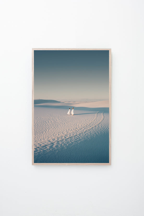 Two people stand in a desert scape, tire tracks beside them, framed on a white wall.