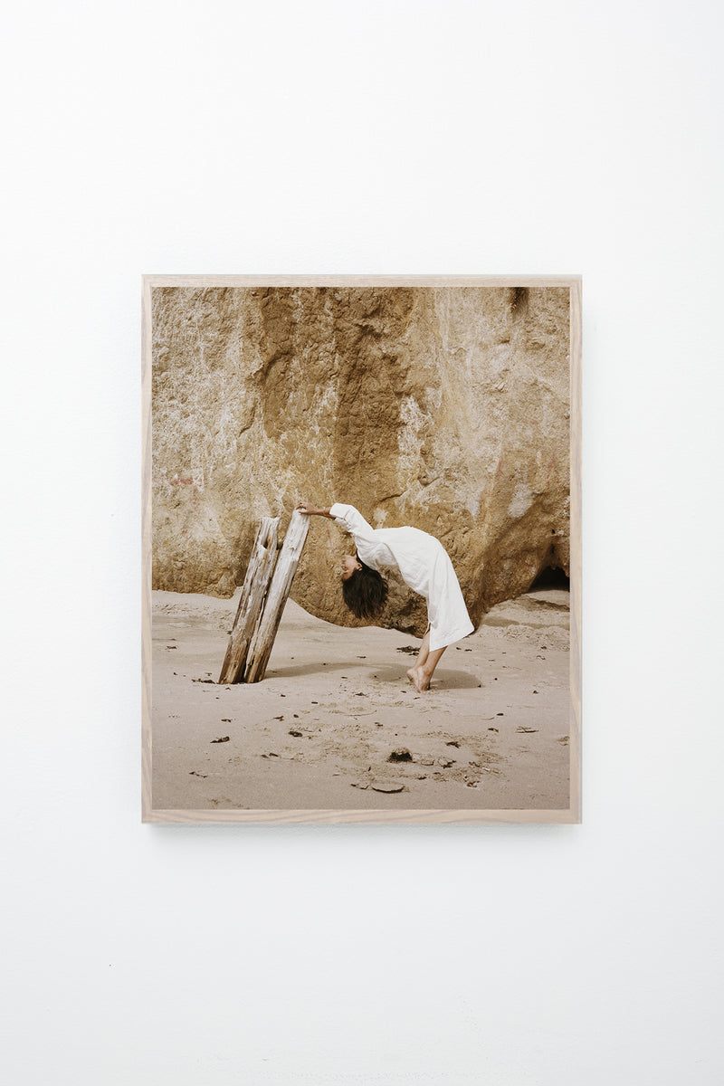 Woman leans backward and grabs onto driftwood, framed on white wall.