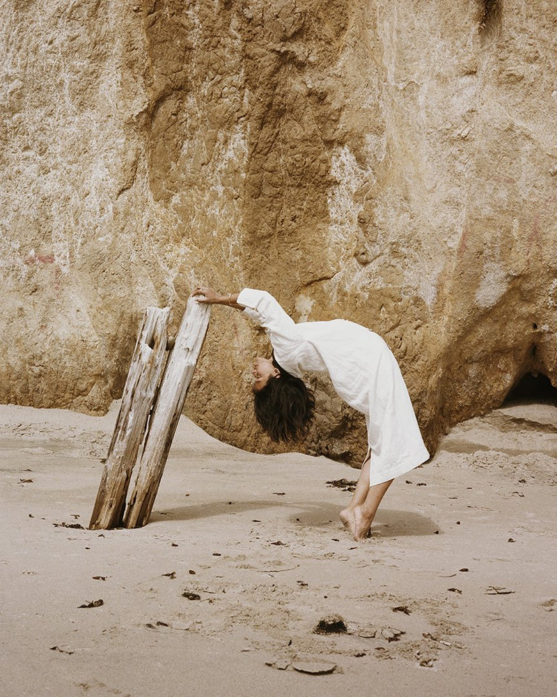 Woman leans backward and grabs onto driftwood.