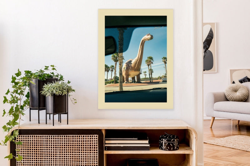 Statue of dinosaur seen through vehicle window, framed in home.