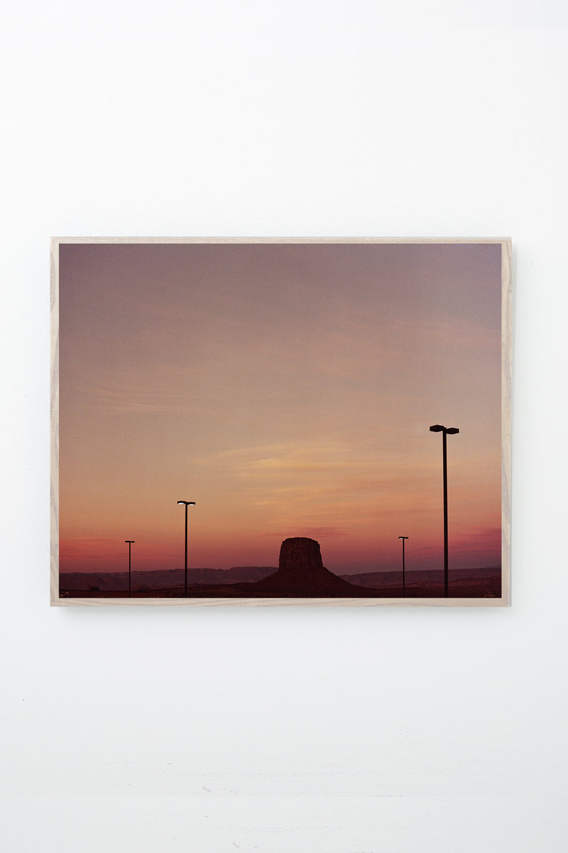 Rock formation extending from the ground at sunset, framed on white wall.