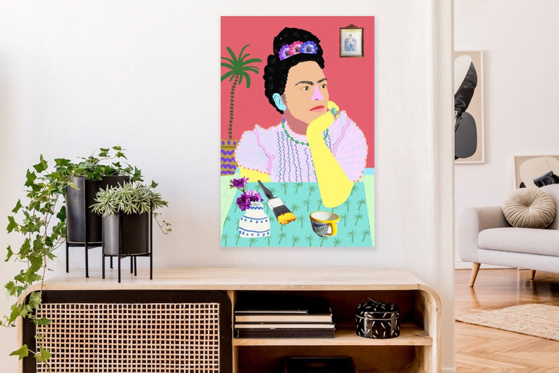 Colourful portrait of Frida Kahlo at table with paintbrush, teacup, and flowers in vase, unframed.