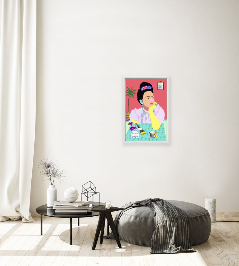 Colourful portrait of Frida Kahlo at table with paintbrush, teacup, and flowers in vase, framed.
