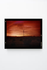 Red sky over desert landscape with telephone poles, framed.