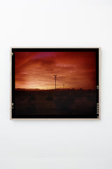 Red sky over desert landscape with telephone poles, framed on white wall.