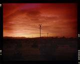 Red sky over desert landscape with telephone poles, unframed.