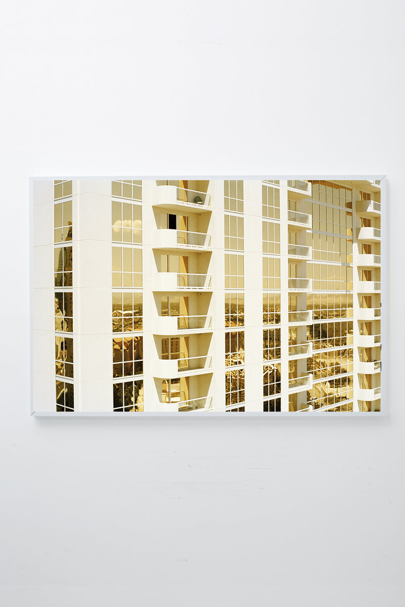 Mirrored windows of apartment building reflect gold light, framed.