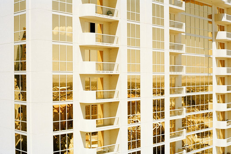 Mirrored windows of apartment building reflect gold light, unframed.
