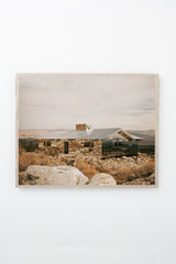 House made of mirrors in a rocky, mountainous landscape, framed on white wall.