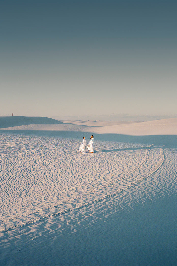 Two people stand in a desert scape, tire tracks beside them.