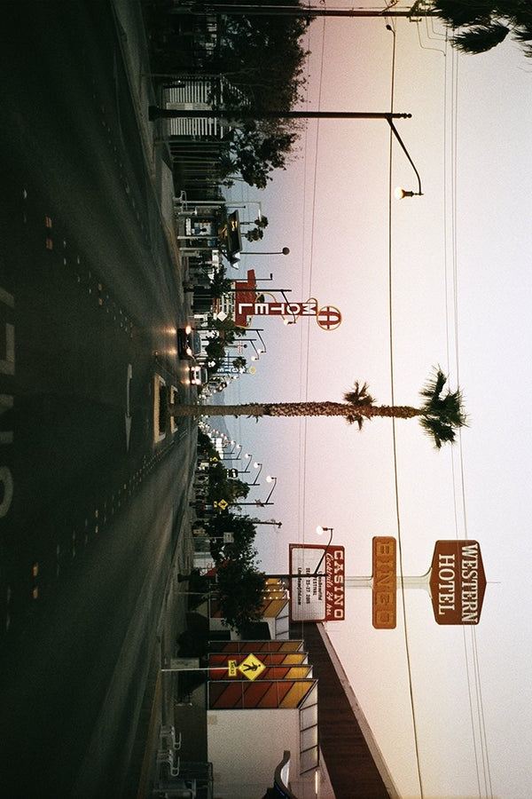 Street lined with casino and motel signs, cars, and palm trees.