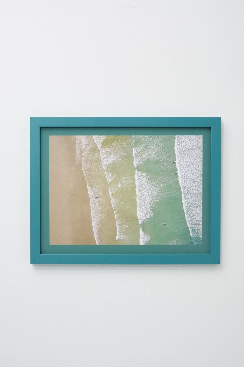 """Ocean"" (Aerial view of water washing up on sand, teal border), framed, hung on white wall."