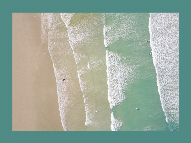 Aerial view of water washing up on sand, teal border.