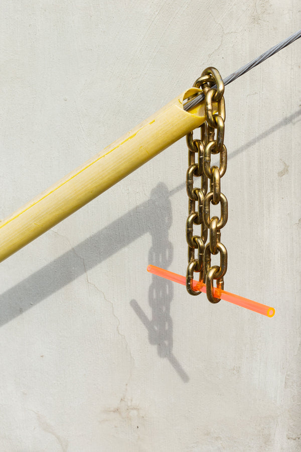 Gold chain and orange straw draped over horizontal wire.