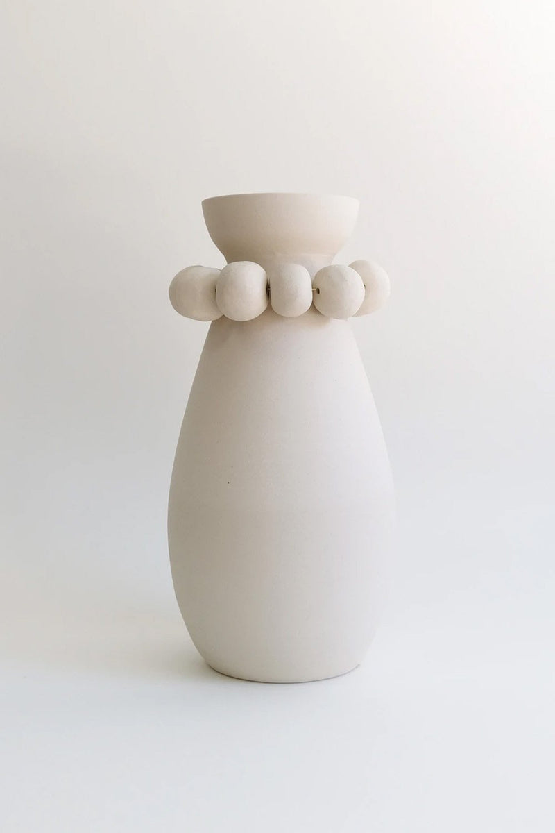 Clay vase with clay bead details around neck.