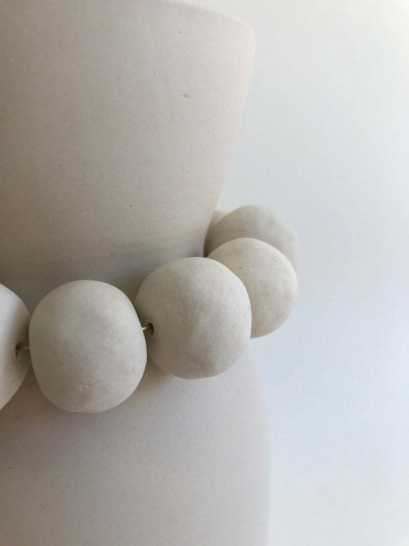 White clay vase with clay beads around neck, bead detail.