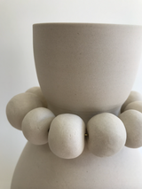 White clay vase with clay beads around neck, detail.