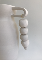White clay vase with handle, beads hanging, bead detail.