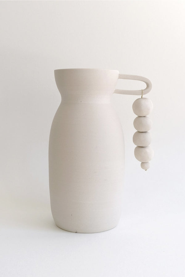 White clay vase with handle, beads hanging.