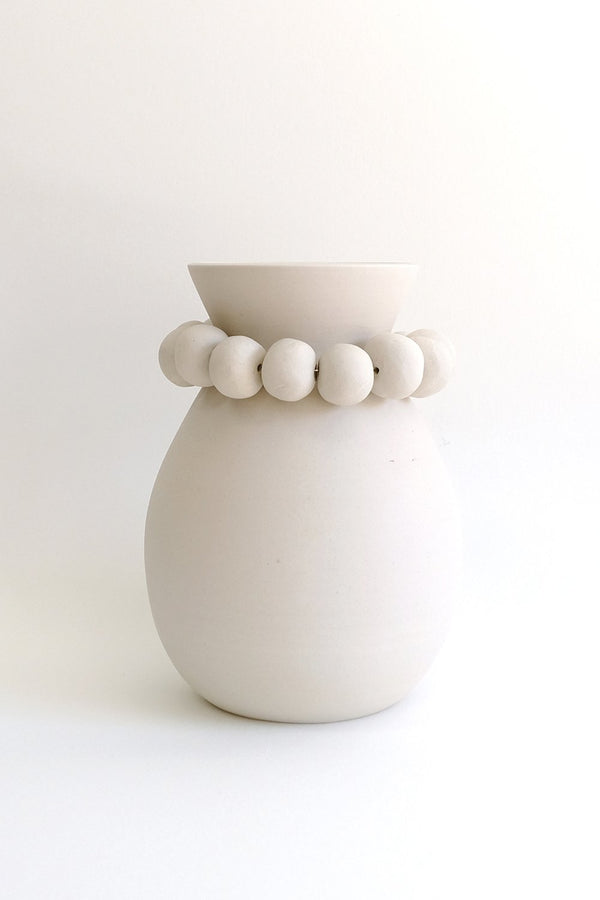 White clay vase with clay beads around neck.