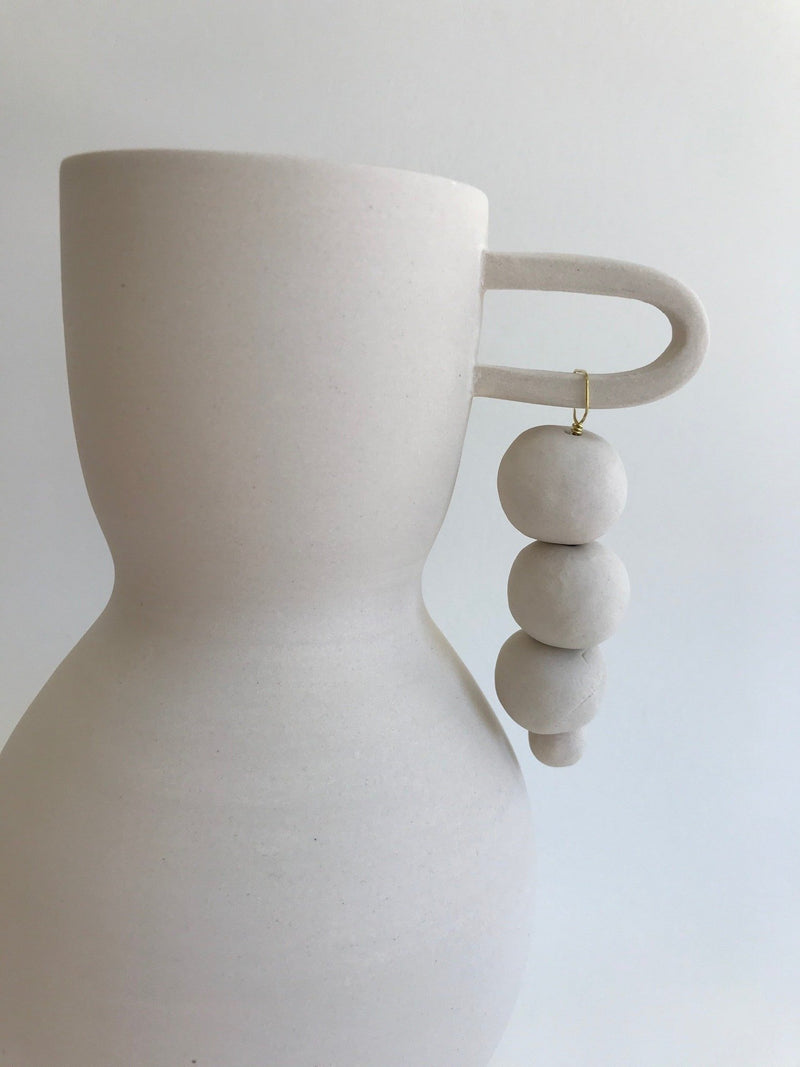 White clay vase with handle and hanging beads, detail.